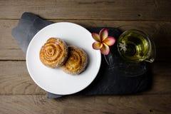 Cynamonowe rolki z chryzantemy herbatą na drewnianym tle Obrazy Royalty Free