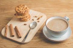 cynamonowi kije, ciastka i filiżanka, coffee/cynamonowi kije, ciastka i filiżanka kawy na drewnianym tle, zdjęcie royalty free