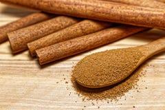 Cynamonowi kije i drewniana łyżka z cynamonu proszkiem na drewnianej bazie Fotografia Stock