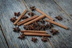 Cynamonowi kije i gwiazdowy anyż na nieociosanym drewnie Zdjęcia Stock