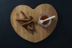 Cynamonowi kije i miód na sercu kształtowali ciapanie deskę Zdjęcia Stock