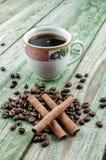 Cynamonowi kije na kawowych adra z filiżanki kawą na zielonym wieśniaka stole Obraz Royalty Free
