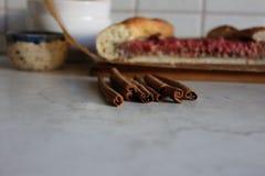 Cynamonowi kije na kuchennym stole z jagodowym kulebiakiem na tle Obraz Royalty Free