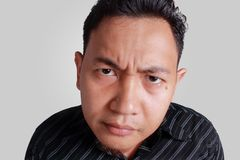 Cynical Asian Man Expression. Headshot portrait of funny Asian man showing cynical unhappy angry facial expression, isolated on grey Stock Images
