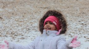 Snow Day. Little Girl Enjoying Playing in the Snow and throwing snow into the air Royalty Free Stock Image