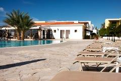 Cypern hotellsikt på solsängar, del av simbassängen och central byggnad arkivbilder