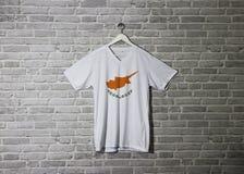 Cypr flaga na koszula i obwieszenie na ?cianie z ceg?? deseniujemy tapet? zdjęcie stock
