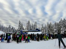 group of skiers and snowboarders waiting in line to hitch a ride up the ski lift on Cypress Mountain royalty free stock photos