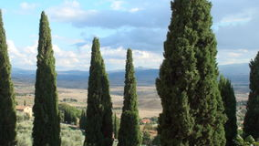 Cypresses. View on the valley of the Val d'Orcia with rain coming in and a lane of cypresses in the foreground stock footage