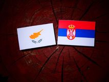 Cypriot flag with Serbian flag on a tree stump isolated. Cypriot flag with Serbian flag on a tree stump stock images