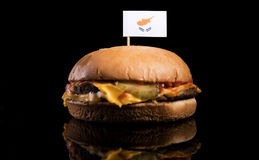 Cypriot flag on top of hamburger isolated on black Royalty Free Stock Image