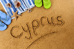Cyprus beach sand word writing. The word Cyprus written on a sandy beach, with beach towel, starfish and flip flops Stock Images