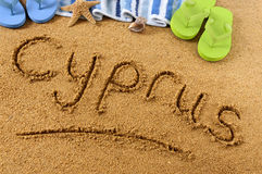 Cyprus beach sand word writing. The word Cyprus written on a sandy beach, with beach towel, starfish and flip flops Royalty Free Stock Image