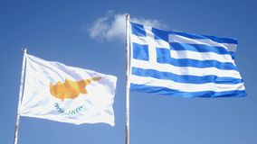 Cyprus flag and Greek flag flapping in wind on a pole. Blue sky and cyprus and greek flags.  stock footage