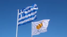 Cyprus and greek flags flapping in wind on a pole. Blue sky, greek and cyprus flag. Slow motion.  stock footage