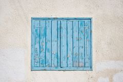 Cyprus, Larnaca. Blue wooden, peeled window, shutters on pink wall. Facade of building, closeup. Cyprus, Larnaca. Blue wooden, peeled window, shutters on pink royalty free stock photography