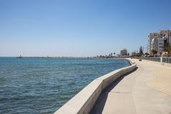 Cyprus, Larnaca city. Stone path around and above the sea. Port, beach, buildings, blue sky backdrop. Stock Images