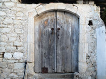 Cyprus Old wooden door with surrounding white stone Stock Photography