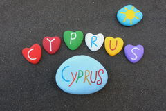 Cyprus, souvenir with multicolored stone hearts over black volcanic sand Stock Images
