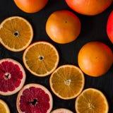 Cytrus flatlay na ciemnym nieociosanym tle Pokrojone i całe pomarańcze i grapefruits fotografia stock