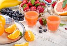 Cytrusa sok, owoc i jagody na drewnianym tle, Zdrowy e obraz royalty free