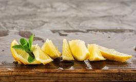 Cytryna i nowi liście słuzyć na drewnianej kuchni desce na betonu stole, składniku dla lato koktajli/lów i lemoniadzie, Fotografia Royalty Free