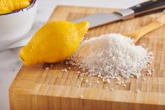Cytryna i stos prostacka morze sól na tnącej desce zdjęcie stock