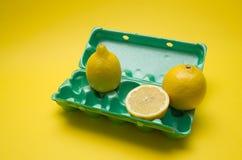 Cytryna w jajecznym kartonie na żółtym tle Fotografia Royalty Free