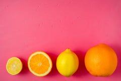 Cytryny i pomarańcze na jaskrawym różowym tle fotografia stock
