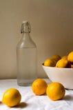 Cytryny i szklana butelka Zdjęcia Royalty Free