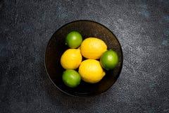 Cytryny i wapno w szklanym pucharze na ciemnym tle Odgórny widok zdjęcie royalty free