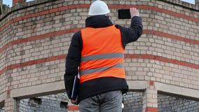 Cywilny inżynier bierze obrazki na pastylka pececie blisko budynku zdjęcie wideo