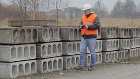 Cywilny inżynier chodzi blisko budowa panel z pastylka pecetem zbiory