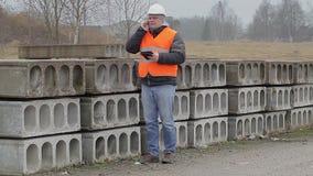 Cywilny inżynier opowiada na telefonie komórkowym blisko budowa panel zbiory