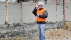 Cywilny inżynier opowiada na telefonie komórkowym blisko niedokończonego budynku zbiory wideo