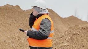 Cywilny inżynier opowiada na telefonie komórkowym przy stosem piasek zbiory