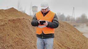 Cywilny inżynier pracuje z pastylka pecetem przy stosem piasek zbiory