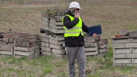 Cywilny inżynier z mądrze telefonem przy miejscem dokąd nowej budowy miejsce zbiory