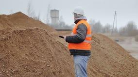 Cywilny inżynier z pastylka pecetem przy stosem piasek zdjęcie wideo