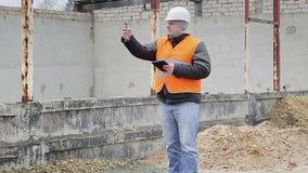 Cywilny inżynier z telefonem komórkowym blisko niedokończonego budynku zbiory