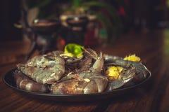 Cząber marynował krewetki dla grilla na czarnym talerzu na drewnianym stole podczas owoce morza kucharstwa Obraz Stock