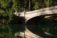 Część łęku most wyraźnie odbija na jeziorze przy central park obrazy royalty free