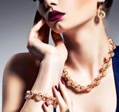 Część żeńska twarz z piękną złotą biżuterią Obrazy Stock