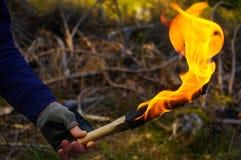 Część mężczyzna i ręka z pochodnią płoniemy w dzikim natury tle Zdjęcie Stock