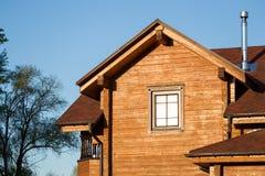 Część nowożytny drewniany dom na wsi z niebieskim niebem na tle Dach eco budynek mieszkalny blisko lasowego budynku Zdjęcia Stock