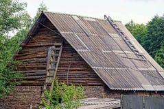 Część starego kraju stajnia z drewnianym szarym attykiem pod łupkowym dachem z drabiną przeciw ścianie obraz royalty free