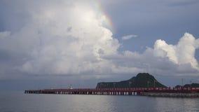 Część tęcza z niebieskim niebem, chmurą nad rewolucjonistka długim mostem i morzem, góra w tle, pokój fala Zdjęcie Stock