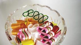Część trzyma kolorowego tasiemkowego cukierek na białym tle puchar fotografia stock