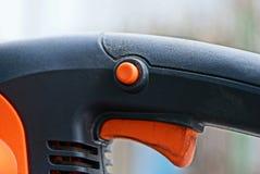 Część władzy narzędzie z pomarańczowym guzikiem i cynglem na czarnej plastikowej rękojeści obrazy stock