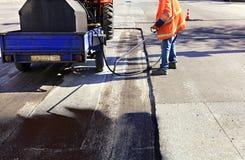 Częściowa naprawa asfaltowa droga Pracownik rozpyla bitum na asfaltowej powierzchni obraz stock